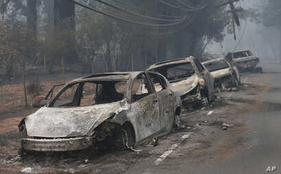 The burned out hulks of cars abandoned by their drivers sit along a road, Nov. 9, 2018, in Paradise, Calif. A massive wildfire swept through the area, Thursday, and the roads were so clogged with vehicles, that some drivers left their cars and ran to...