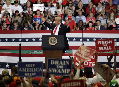 President Donald Trump reacts as supporters wave signs during a rally, Oct. 31, 2018, in Estero, Fla.