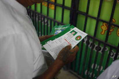 A member of military-backed Union Solidarity and Development Party holds leaflets promoting a candidate of USDP during an election campaign in Mandalay, the second largest city in Myanmar, Oct. 18, 2015.