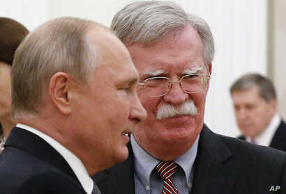 Russian President Vladimir Putin, left, and U.S. President Donald Trump's National Security Adviser John Bolton are seen during their meeting in the Kremlin, in Moscow, Russia, Oct. 23, 2018.