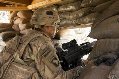In this Sept. 8, 2016 photo, a U.S. Army soldier guards a position at Camp Swift, northern Iraq. U.S. troops will be engaged more closely than ever in fighting against Islamic State group militants as they back Iraqi forces in the long-anticipated as...