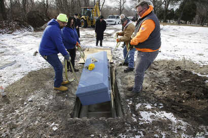 Cemetery personnel lower the casket containing the body of 82-year-old James Oram, who died in a local nursing home and whose body was unclaimed, into his unmarked grave on the perimeter of Hope Cemetery in Worcester, Massachussets, Feb. 1, 2018.