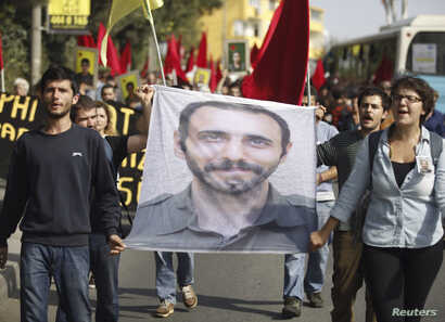 FILE - Students carry a portrait of Nejat Agirnasli, a People's Protection Unit (YPG) fighter who was killed during clashes with Islamic State militants in Kobani, during ceremony held in his memory at Bosphorus University in Istanbul, Oct. 17, 2014....