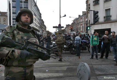 French soldiers secure the area as shots are exchanged in Saint-Denis, France, near Paris, Nov. 18, 2015 during an operation to catch fugitives from Friday night's deadly attacks in the French capital.