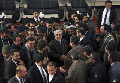 Afghanistan Chief Executive Abdullah Abdullah, center, shakes hands with his supporters after arriving to register as a candidate for the presidential election, at the Independent Elections Commission, in Kabul, Jan. 20, 2019.