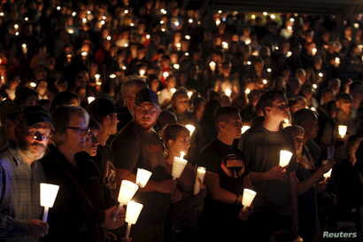 People take part in candlelight vigil following a mass shooting at Umpqua Community College in Roseburg, Oregon Oct. 1, 2015.