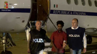 Medhane Tesfamariam Berhe is pictured with Italian policemen as they land at Palermo airport, Italy, following his arrest in Khartoum, Sudan, on May 24, in this file photo released June 8, 2016 by Italian police. Image pixelated at source.