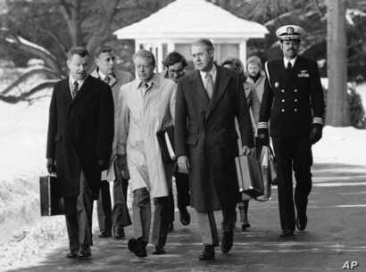 FILE - President Jimmy Carter, flanked by Secretary of State Cyrus (right) and his adviser on foreign policy, Zbigniew Brzezinski (left), walk toward a waiting helicopter to fly to the nearby Andrews Air Force Base, Md.