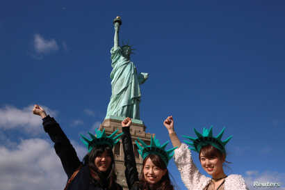 Japanese tourists pose in front of the Statue of Liberty on the 130th anniversary of the dedication in New York Harbor, in New York City, October 28, 2016.