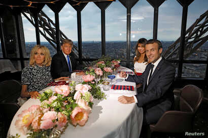 Brigitte Macron, left, wife of French President Emmanuel Macron, right, U.S. President Donald Trump and first lady Melania Trump pose at their table at the Jules Verne restaurant for a private dinner at the Eiffel Tower in Paris, July 13, 2107.