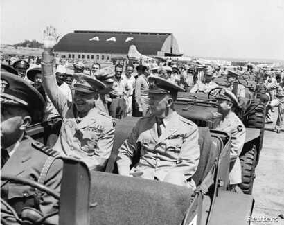 Gen. Dwight D. Eisenhower (L) sits in the back of a jeep with U.S. Army Chief of Staff General George C. Marshall, as he waves to spectators at the Washington National Airport in Arlington, Virginia, on June 18 1945, in this handout photo from the US...
