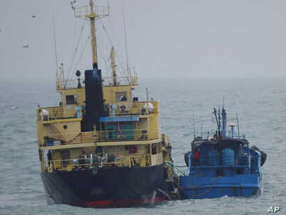 """FILE - This photo released by Japan's Ministry of Defense shows what it says is the North Korean-flagged tanker Yu Jong 2, left, and the Min Ning De You 078 lying alongside in the East China Sea, Feb. 16, 2018. China said it was """"highly concerned"""" ab..."""