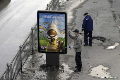 FILE - A worker puts up a billboard showing an image that resembles U.S. President Barack Obama, in Yekaterinburg, Russia, March 31, 2009. A Russian advertising agency has used an image resembling Obama to promote a new vanilla-and-chocolate ice crea...