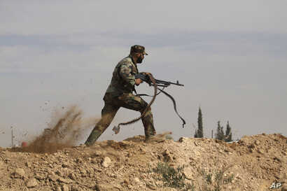 A Shi'ite fighter clashes with members of the Sunni-dominated Free Syrian Army rebel in the town of Hatita, in the countryside of Damascus, Syria, Nov. 22, 2013.
