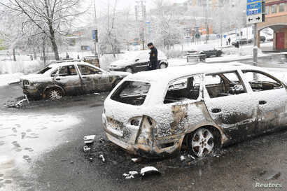 A policeman investigates a damaged car in the Rinkeby suburb outside Stockholm, Sweden, Feb. 21, 2017.