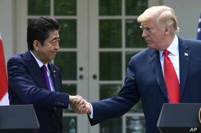 President Donald Trump and Japanese Prime Minister Shinzo Abe shakes hands during a news conference in the Rose Garden of the White House in Washington, June 7, 2018.
