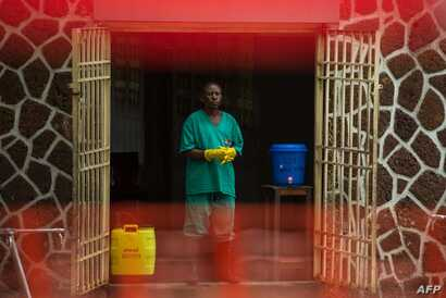 An attendant charged to handle the access to the Ebola security zone stands at the entrance of the Wangata Reference Hospital in Mbandaka, Democratic Republic of the Congo, May 20, 2018.