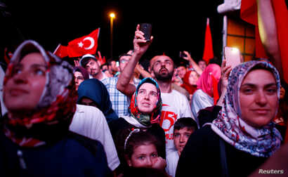 People listen to the speech of Turkey's President Recep Tayyip Erdogan during a ceremony marking the first anniversary of a coup attempt at the Bosporus Bridge in Istanbul, July 15, 2017.