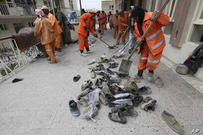 Afghan Municipality workers collect shoes of victims in front the Baqir-ul Ulom mosque after a suicide attack, in Kabul, Afghanistan, Nov. 21, 2016.