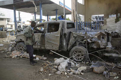 A Somali security man looks at the wreckage of a truck near the Nasahablood hotel in Mogadishu, Somalia, June 26, 2016. The Islamic extremist group al-Shabab claimed responsibility for the damage, inflicted in an attack the day before.