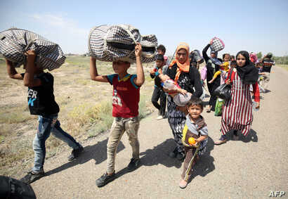Iraqi families are seen near al-Sejar village in Anbar province, after fleeing the city of Fallujah, May 27, 2016, during a major operation by pro-government forces to retake the city from the Islamic State (IS) group.