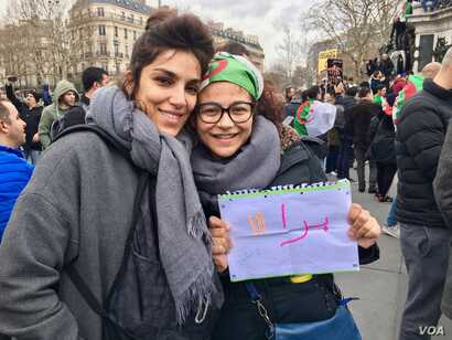 Algerian Yasmine Bouaouiche (R), protesting in Paris, wants France to cut ties with Algeria's government.