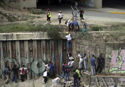 Demonstrators climb a wall to avoid Bolivarian National Guard officers who fired tear gas during a protest in Caracas, Venezuela, April 8, 2017. Opponents of President Nicolas Maduro protested on the streets of the capital as part of a movement that ...