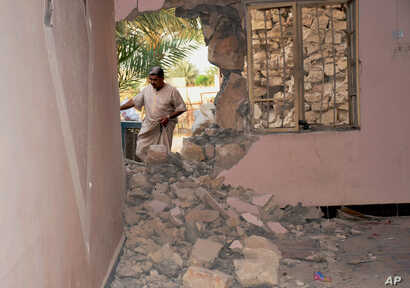 A man inspects his house damaged after a bomb attack by Islamic State group extremists in Khalidiya, 60 miles (100 kilometers) west of Baghdad, Iraq, Sept. 20, 2015.