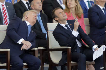 French President Emmanuel Macron, right, and U.S. President Donald Trump watch the traditional Bastille Day military parade, including military jet flyovers, on the Champs Elysees, in Paris, July 14, 2017.
