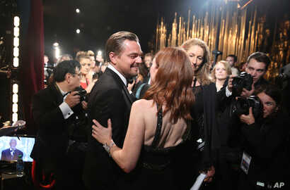 "Leonardo DiCaprio, winner of the award for best actor in a leading role for ""The Revenant"", left, and Julianne Moore appear backstage at the Oscars, Feb. 28, 2016, at the Dolby Theatre in Los Angeles."