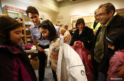 Canada's Prime Minister Justin Trudeau helps a young Syrian refugee try on a winter coat after she arrived with her family from Beirut at the Toronto Pearson International Airport in Mississauga, Ontario, Canada, Dec. 11, 2015.