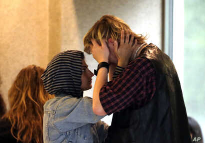 A young woman comforts a crying man outside the courtroom after Jeremy Christian was arraigned in Portland, Ore., May 30, 2017.