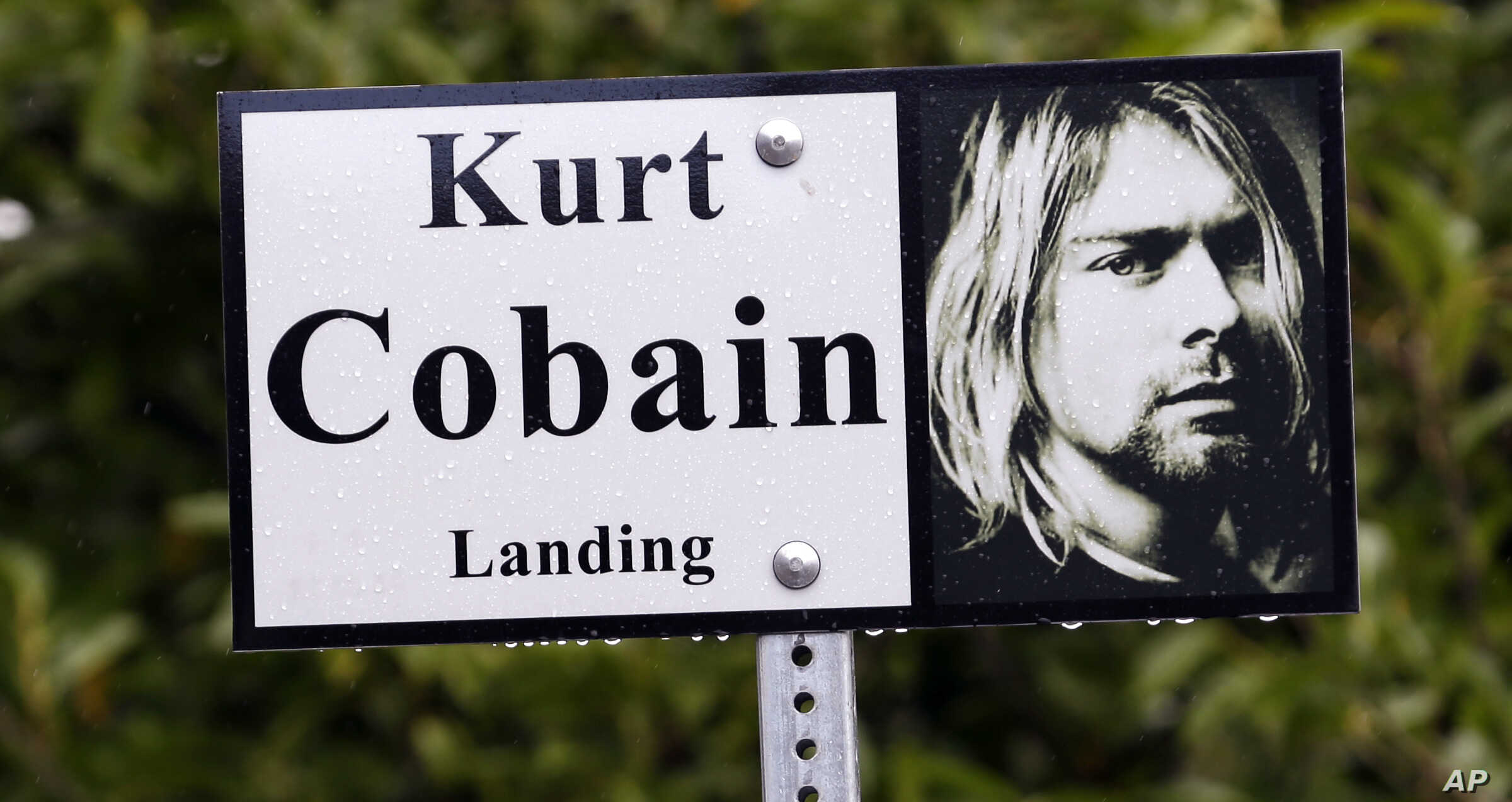 """In this photo taken Monday, Sept. 23, 2013, a sign marks the location of """"Kurt Cobain Landing,"""" a tiny park blocks from the childhood home of Kurt Cobain, the late frontman of Nirvana, in Aberdeen, Wash."""