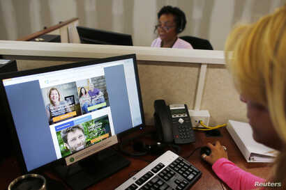 """Janet Perez (R) oversees specialists (top) as they help callers and potential customers find health insurance at a customer contact and call center for HealthSource RI, Rhode Island's health insurance exchange program for the Affordable Care Act or """"..."""