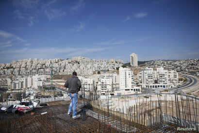Laborer stands on apartment building construction site in Jewish settlement known to Israelis as Har Homa and to Palestinians as Jabal Abu Ghneim, West Bank, Oct. 28, 2014.