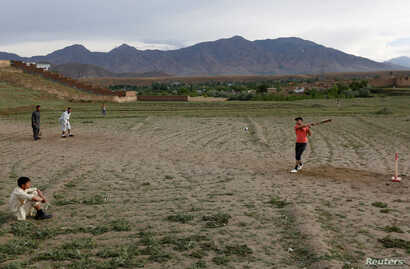 FILE - Afghan men play cricket on outskirt of Kabul, Afghanistan, May 15, 2017.