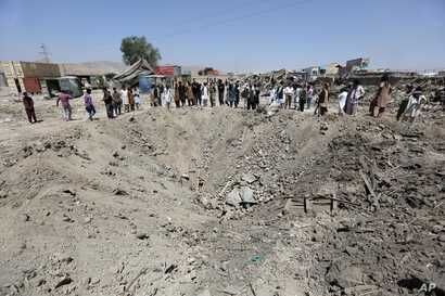 FILE - In this Monday, Aug. 1, 2016 file photo, Afghans look at a crater caused by a truck bombing, in Kabul, Afghanistan.