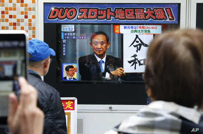"""People watch a TV screen showing the name of new era """"Reiwa"""" is unveiled in a news program in Tokyo, Monday, April 1, 2019."""