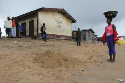 Seen in the background is the only public toilet in West Point, Monrovia, Liberia, Sept. 25, 2014. (Benno Muchler /VOA)