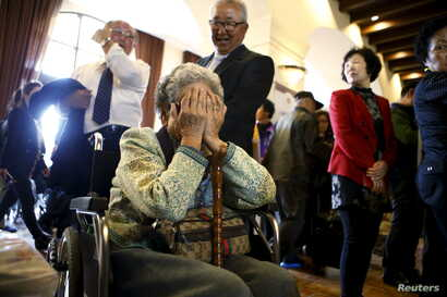 A woman who was selected as a participant for a reunion with family in North Korea reacts at the hotel used as a waiting place in Sokcho, South Korea, Oct. 19, 2015. The reunion of 90 South Koreans and 96 North Koreans will take place Tuesday in the ...
