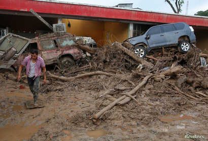 A man walks among the ruins after flooding and mudslides, caused by heavy rains leading several rivers to overflow, pushing sediment and rocks into buildings and roads, in Mocoa, Colombia, April 2, 2017.