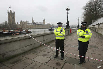 Police guard a cordon on the embankment with Britain's Houses of Parliament, left, in London, March 23, 2017, after attacks in London Wednesday.