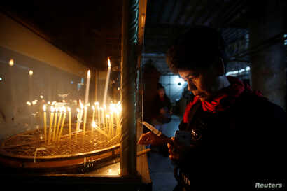 A visitor lights a candle inside the Church of the Nativity on Christmas in the West Bank town of Bethlehem, Dec. 25, 2016.