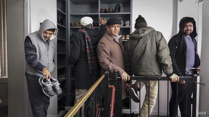 Ahmadi worshippers collect their shoes and belongings after prayer at Masjid Bait Ul Tahir, in Brooklyn. (R. Taylor/VOA)