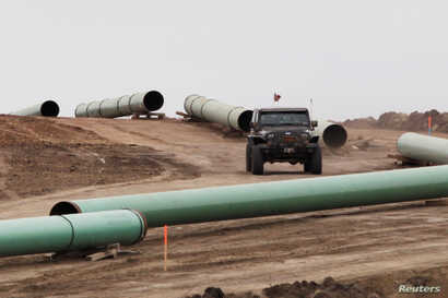 FILE - A vehicle drives next to a series of pipes at a Dakota Access construction site near the town of Cannon Ball, North Dakota, Oct. 30, 2016.