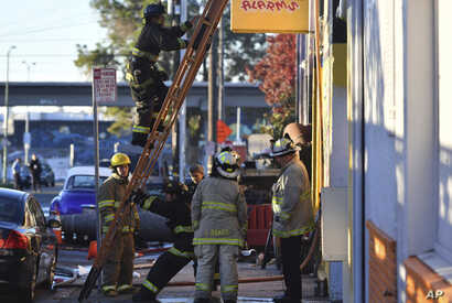 Firefighters assess the scene where a fire tore through a warehouse party early Saturday, Dec. 3, 2016 in Oakland.