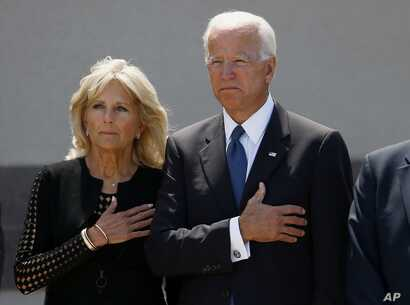 Former Vice President Joe Biden, right, and his wife Jill Biden, pause with hands over their hearts as they watch a military honor guard place the casket of Sen. John McCain, R-Ariz., into a hearse after a memorial service at North Phoenix Baptist Ch...