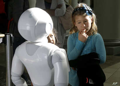 Emerson Hill, 6, interacts with Pepper the robot at Westfield Mall in San Francisco, Dec. 22, 2016.