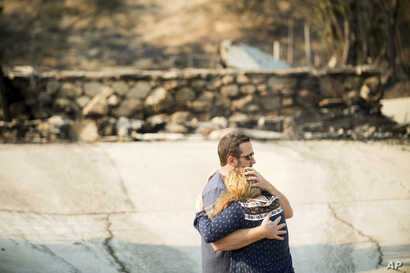 Paul and Erica Mattesich embrace before sifting through rubble at their Ventura, Calif., home, Dec. 6, 2017.