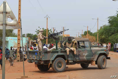 Malian soldiers ride on a pick-up truck with a machine gun after a suicide car bomb attack overnight in Gao, Nov. 13, 2018.